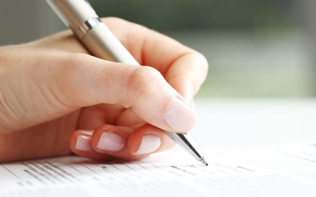 Main de femme qui rempli un formulaire
