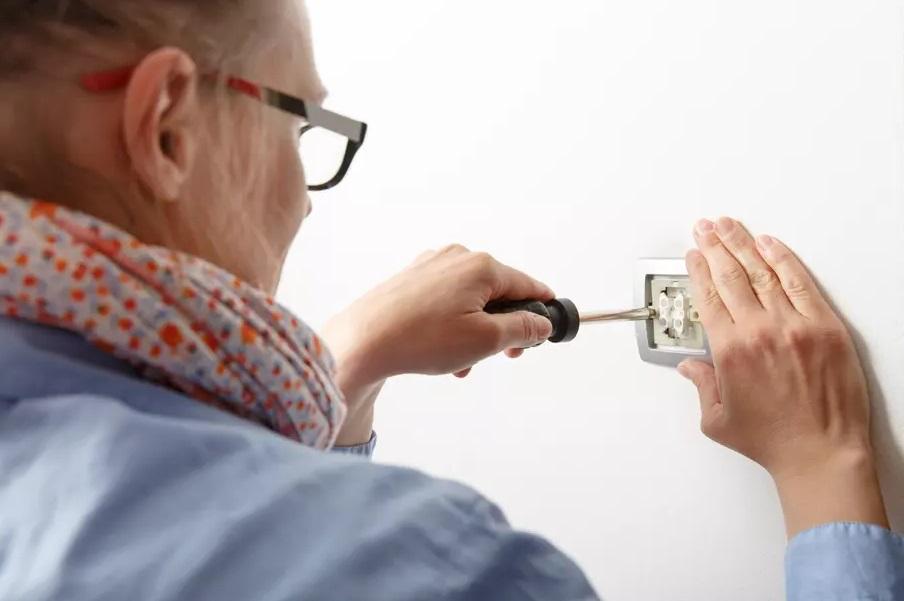 Femme branchant un interrupteur
