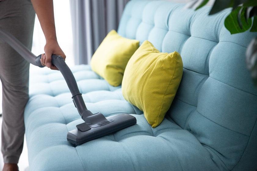 Femme passant l'aspirateur sur un canapé bleu