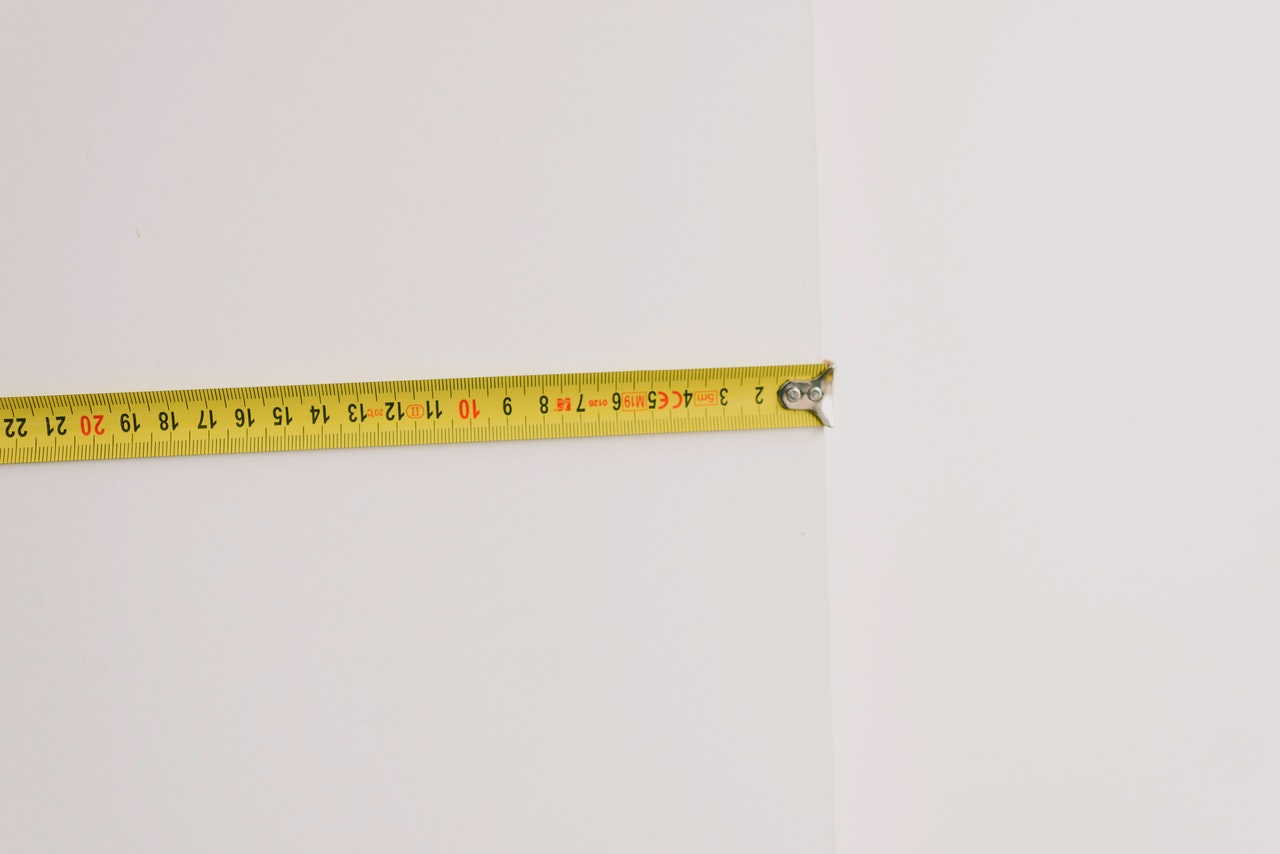 mètre jaune sur mur blanc calculer volume ou superficie